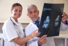 男性和女性医生微笑的审查的X-射线te 免版税库存图片