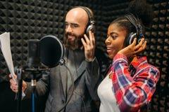 男性和女歌手在录音演播室 免版税库存图片