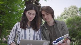 男性和女生坐在长凳、女孩藏品膝上型计算机和男孩的便服的有学报在手 影视素材