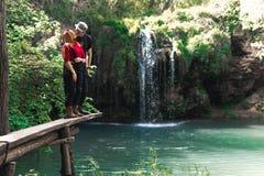 男性和妇女,愉快的夫妇摩托车骑士旅客 旅行自然森林,山,在背景的美丽的瀑布 ?? 免版税图库摄影
