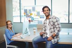 男性图表设计师坐有工友的书桌在会议室 库存照片