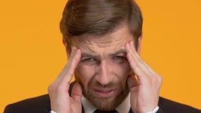 男性在他的头的感觉锐痛,在寺庙的痉孪,劳累过度,特写镜头 股票录像