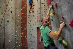 男性在健身俱乐部的运动员上升的墙壁画象  库存图片