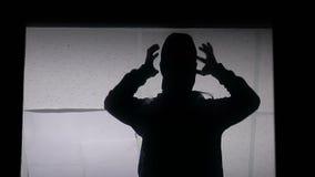 男性在偷窃前的泽鳄佩带的巴拉克拉法帽,夜贼剪影在窗口里 股票视频