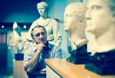 男性在历史博物馆评估陈列 库存图片
