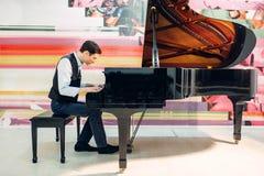 男性在大平台钢琴的钢琴演奏家实践的构成 免版税图库摄影