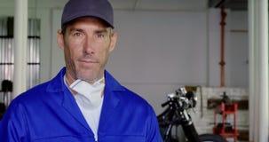 男性在摩托车修理车库4k的技工佩带的制服 股票录像