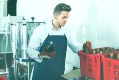 男性在汽酒工厂的工作者包装的酒瓶 免版税库存图片