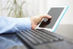 男性在片剂工作和个人计算机 免版税图库摄影