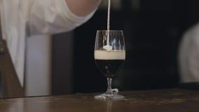男性在玻璃的侍酒者倾吐的牛奶与酒精和咖啡女性访客的使用特定工具,因此它 股票录像