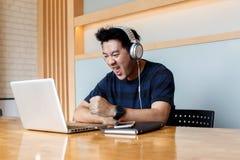 男性在社会网络的博客作者观看的录影通过耳机,当更新在便携式计算机,亚裔人听的audi上时的软件 库存照片