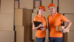 男性在站立反对棕色纸板箱backround的橙色制服的anf女性传讯者 运送公司职员, 4K 影视素材