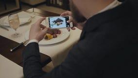 男性在餐馆桌里和大牛排的制造照片坐他的板材 从的射击供以人员后部 股票视频