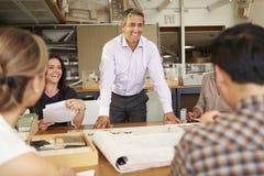 男性坐在表上的建筑师上司主导的会议  免版税图库摄影