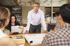 男性坐在表上的建筑师上司主导的会议  免版税库存图片