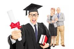 男性大学毕业生和他骄傲的父母 免版税图库摄影