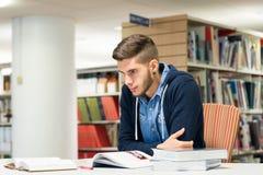 男性大学生在图书馆里 免版税库存照片