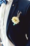 男性婚礼衣裳细节  在蓝色衣服、白色衬衣和蓝色蝶形领结的人别住的美丽的钮扣眼上插的花 免版税库存图片