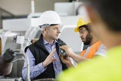 男性审查员有与工作者的讨论在金属工业 免版税库存图片