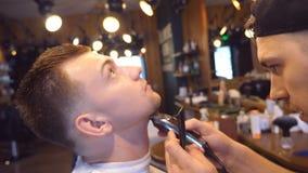 男性客户饰物胡子有飞剪机的在理发店 发型过程 关闭慢动作 影视素材