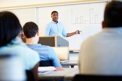 男性家庭教师教的大学生在教室 免版税图库摄影