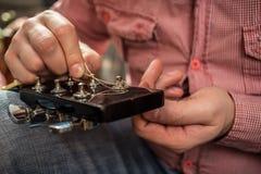 男性对声学吉他的插入物新的吉他串 免版税库存图片