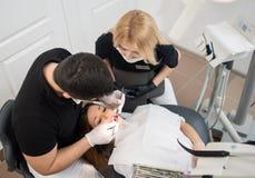 男性对待耐心牙的牙医和女性助理与牙齿工具-在牙齿诊所办公室反映并且探查 图库摄影