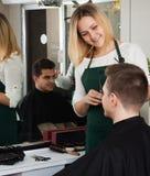 男性少年和微笑的年轻美发师切口头发 免版税库存照片
