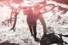 男性山骑自行车的人运载的自行车大角度看法在森林里 免版税库存照片