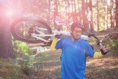 男性山骑自行车的人运载的自行车,当走时 图库摄影
