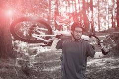 男性山骑自行车的人运载的自行车,当走时 库存图片