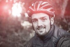 男性山骑自行车的人画象在森林里 免版税库存照片