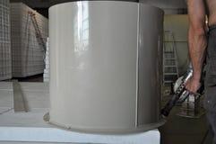 男性工作者密封一辆圆柱形定制的塑料坦克在小制造业 库存照片