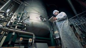 男性工作者控制酿造设备的作用的过程 股票录像