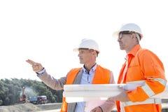 男性工程师谈论在建造场所反对清楚的天空 库存图片