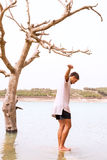 年轻男性平衡在一个岩石在一个被充斥的湖 库存图片