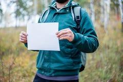 男性徒步旅行者拿着您能插入您的文本的白皮书 库存图片