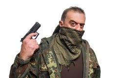 男性恐怖分子军事夹克 枪在他的手上 库存照片