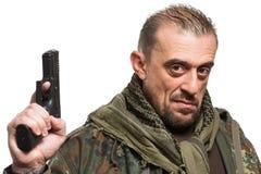 男性恐怖分子军事夹克 枪在他的手上 免版税库存图片