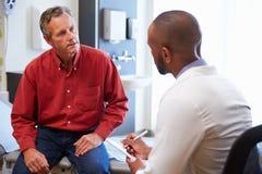 男性患者和Have Consultation In医生医房 免版税图库摄影