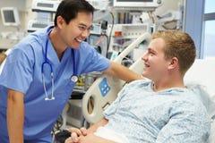 年轻男性患者谈话与男性护士在急诊室 图库摄影