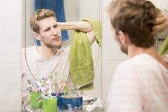 男性成人舒展在镜子前面在卫生间里在早晨 免版税库存照片