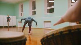 男性战斗机执行军事把戏与在播放一两个乐器jembe的背景的舞蹈元素或 股票录像