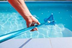 男性手举行水池网擦净剂 图库摄影
