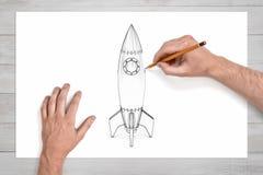 男性手使用一支铅笔画有一块圆的反光板的一艘太空火箭 库存图片