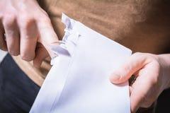 男性手剥去打开不耐烦的信封的边缘-等待消息概念 免版税库存图片