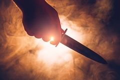 男性手剪影举行刀子、人凶手或者疯狂概念 库存图片