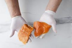 男性手和三文鱼几个可口,但是未加工的片断顶视图反对白色厨房用桌的 图库摄影