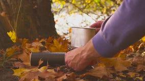 男性手在煤气炉做食物或热的饮料在秋天森林里在湖附近 影视素材