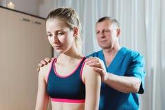 男性手工发自内心的治疗师男按摩师治疗一名年轻女性患者 肩膀和前臂的诊断 库存图片